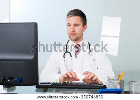 Portrait Of A Male Doctor Using Computer In Clinic