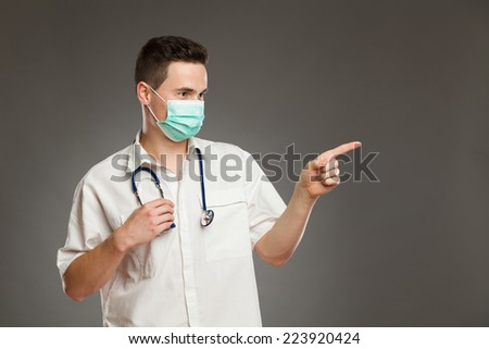Portrait of a male doctor wearing surgical mask and pointing at copy space. Waist up studio shot on gray background. - stock photo