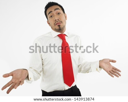 Portrait of a male executive shrugging off against white background - stock photo