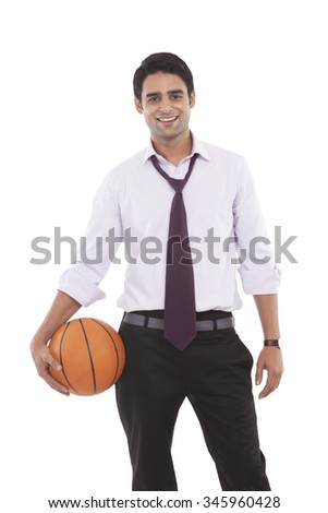 Portrait of a male executive with a basketball - stock photo