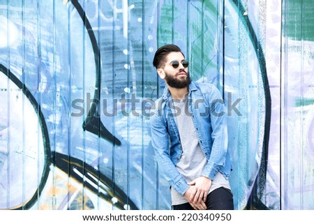 Portrait of a male fashion model with  sunglasses posing by graffiti  - stock photo