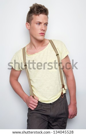 Portrait of a male fashion model with suspenders - stock photo