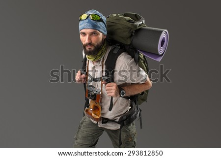 Portrait of a male fully equipped tourist with backpack and the camera on gray background. side view. tourist looking into the camera - stock photo