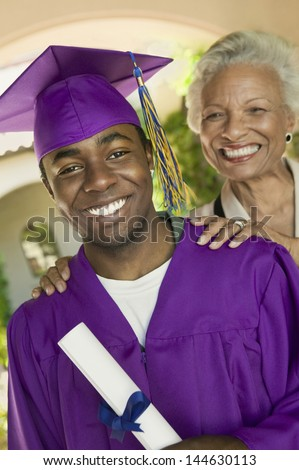 Portrait of a male graduate with his happy grandmother standing outside