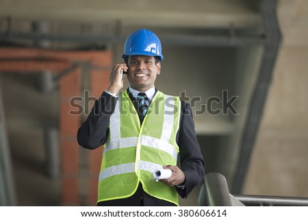 Portrait of a male Indian Architect or industrial engineer at work using phone.