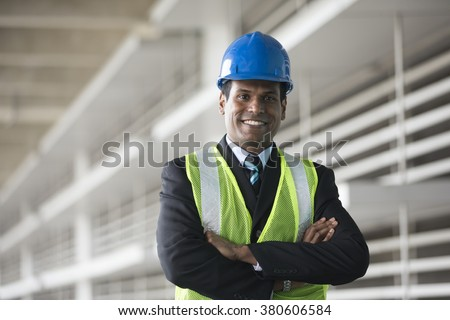 Portrait of a male Indian, industrial engineer at work. Asian engineer smiling & looking at the camera.