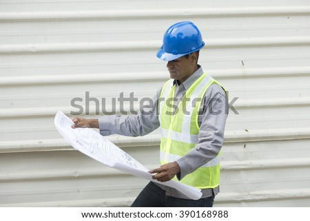 Portrait of a male Indian industrial engineer at work looking at technical drawing plans.