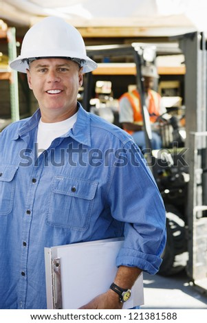 Portrait of a male industrial worker holding clipboard with coworker in the background