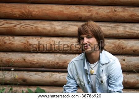 Portrait of a male model standing in front of a wooden house - stock photo