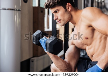 Portrait of a male muscular bodybuilder workout with dumbbell in fitness gym - stock photo