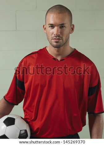 Portrait of a male soccer player holding ball against green wall - stock photo