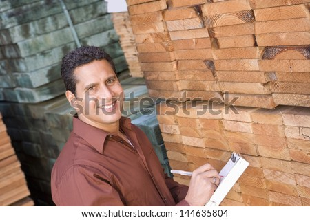 Portrait of a male supervisor stock taking in warehouse - stock photo