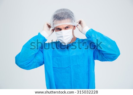 Portrait of a male surgeon standing isolated on a white backgorund and looking at camera - stock photo