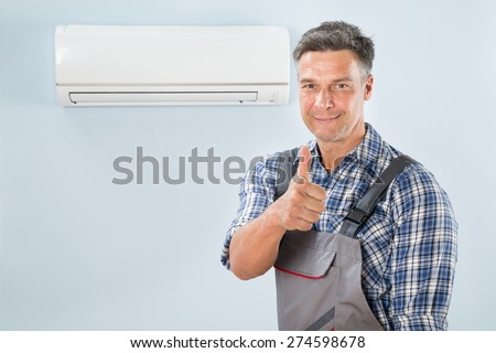 Portrait Of A Male Technician Gesturing Thumb Up - stock photo
