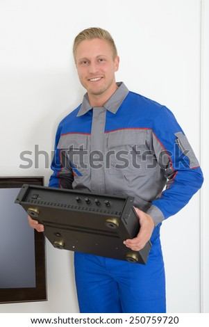 Portrait Of A Male Technician Holding Amplifier