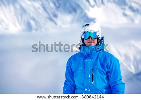 Portrait of a male tourist in ski outfit, goggles and helmet at the winter resort - stock photo