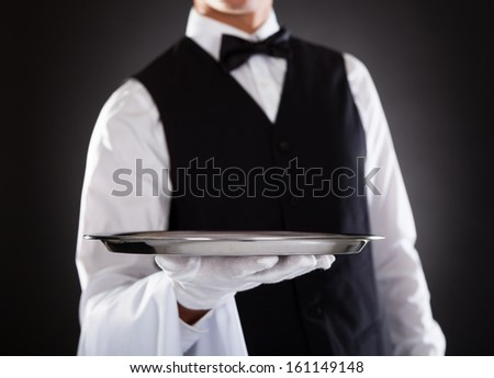 Portrait Of A Male Waiter Holding Tray Over Black Background - stock photo