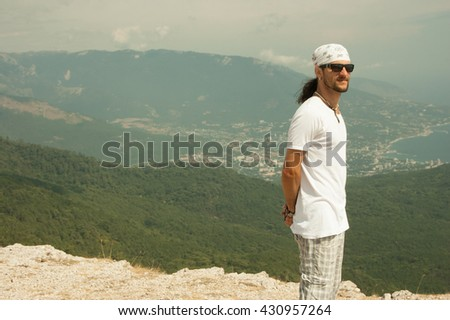 portrait of a man against the backdrop of the mountains - stock photo