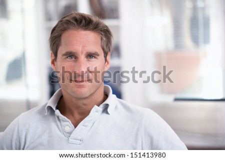 Portrait of a man alone on couch, At Home, Looking To Camera Smiling - stock photo
