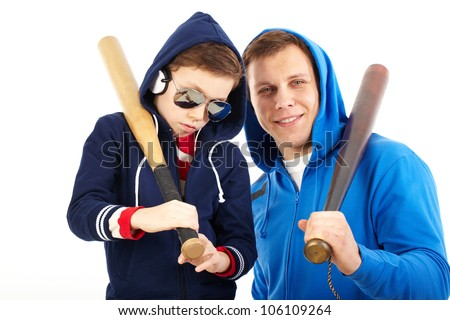 Portrait of a man and a boy holding baseball bats isolated against white background - stock photo