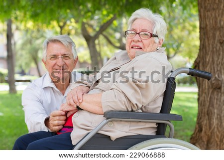 Portrait of a man and senior woman in wheel chair at the park. looking at camera with limited dof - stock photo