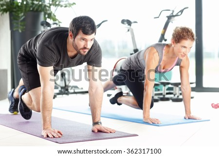 Portrait of a man and woman doing plank exercises at the gym. - stock photo