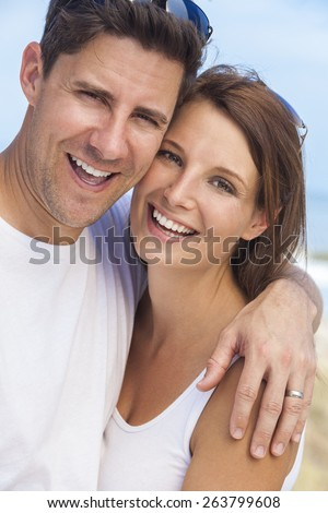 Portrait of a  man and woman romantic couple in white clothes embracing and laughing with oerfect smiles on a beach with bright clear blue sky