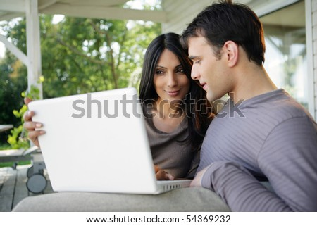 Portrait of a man and woman sitting on a sofa with a laptop computer
