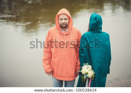 portrait of a man and woman with flowers, in raincoats, on the background of the river .