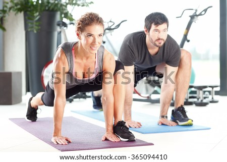 Portrait of a man and woman working out at the gym. Training to become fit.  - stock photo