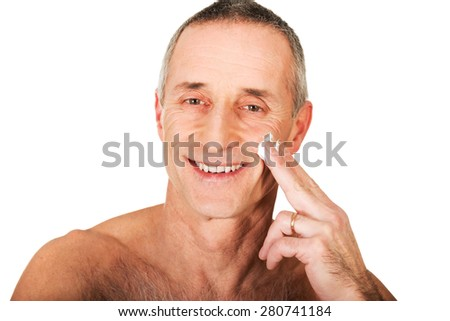 Portrait of a man applying cream on his face. - stock photo