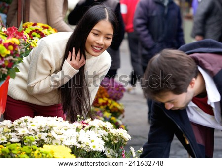 Portrait of a man buying flowers for his girlfriend at flower shop  - stock photo