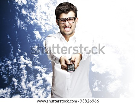 portrait of a man changing channel with a remote control against a sky background - stock photo