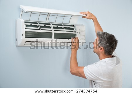 Portrait Of A Man Cleaning Air Conditioning System - stock photo