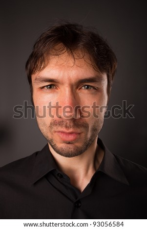 portrait of a man close up in a black shirt on a black background - stock photo