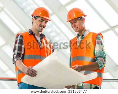 Portrait of a man construction builder in yellow helmet and vest the office center