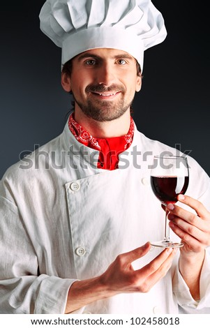 Portrait of a man cook holding a glass of red wine. Shot in a studio. - stock photo