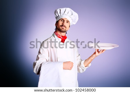 Portrait of a man cook holding a plate. Shot in a studio. - stock photo