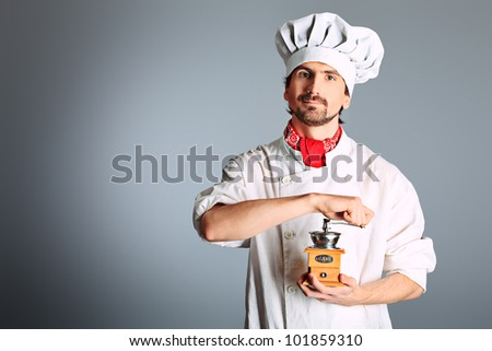 Portrait of a man cook holding coffee grinder. Shot in a studio. - stock photo