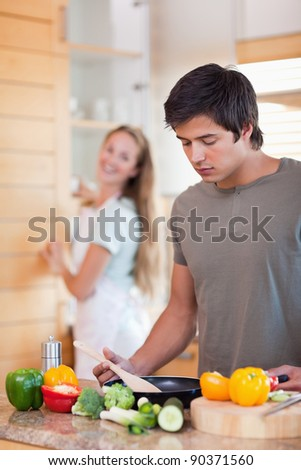 Portrait of a man cooking while his wife is washing the dishes in their kitchen - stock photo