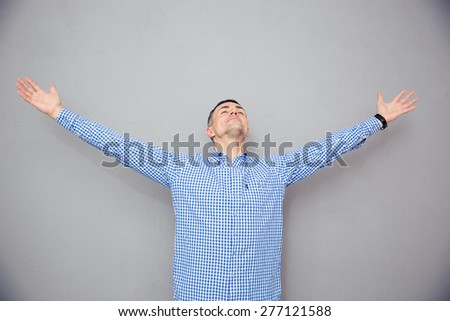 Portrait of a man gesturing freedom expression over gray background - stock photo