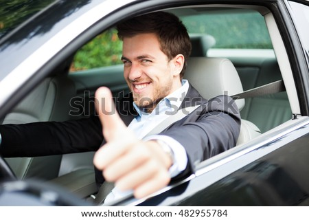 Portrait of a man giving thumbs up while guy driving his car