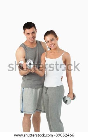 Portrait of a man helping a gorgeous woman to work out against a white background