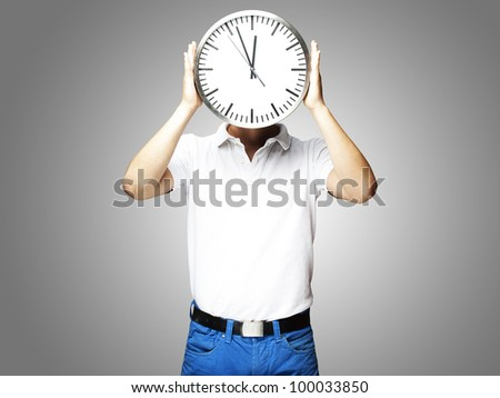 portrait of a man holding a clock against a grey background - stock photo