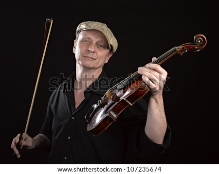 Portrait of a man holding a  wooden violin on black background - stock photo