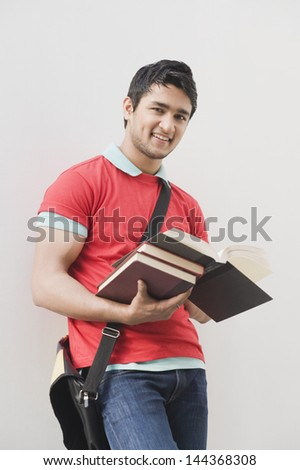 Portrait of a man holding books and smiling - stock photo