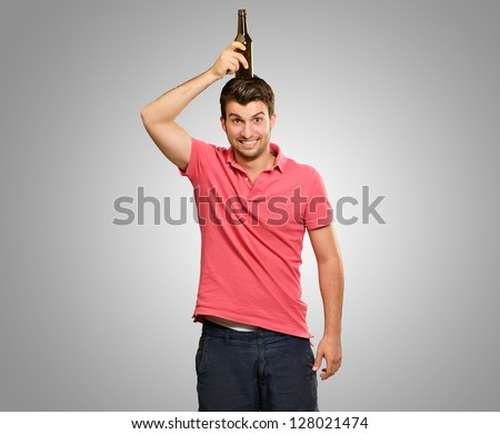 Portrait Of A Man Holding Bottle On Head On Background - stock photo