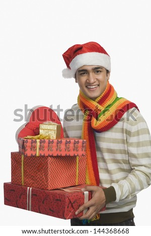 Portrait of a man holding Christmas presents - stock photo