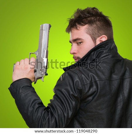 Portrait Of A Man Holding Gun against a green background