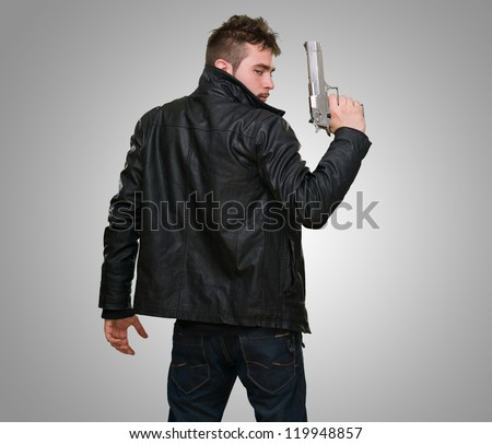 Portrait Of A Man Holding Gun against a grey background